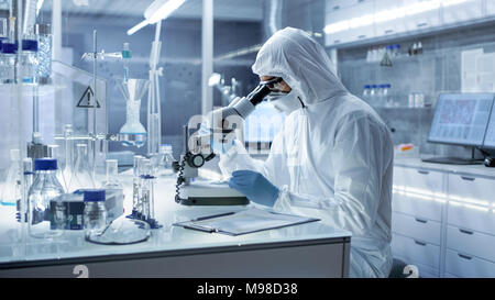 In a Secure High Level Research Laboratory Scientist in a Coverall Examines Petri Dish Under Microscope. - Stock Photo