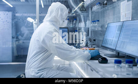 In a Secure High Level Laboratory Scientists in a Coverall Conducting a Research. Biologist Analyzes Results on a Computer. - Stock Photo