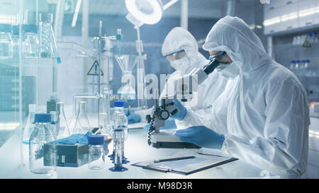 In a Secure High Level Laboratory Scientists in a Coverall Conducting a Research. Chemist Adjusts Samples a  Petri Dish with Pincers and then Examins - Stock Photo
