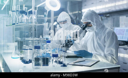 In a Secure High Level Laboratory Scientists in a Coverall Conducting a Research. Chemist Adjusts Samples in Petri Dish with Pincers and then Examins - Stock Photo