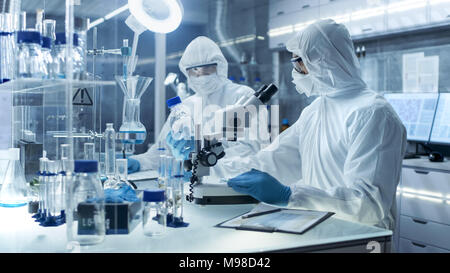In a Secure High Level Laboratory Scientists in a Coverall Conducting a Research. Chemist Adjusts Samples and Discuss Experiment with Collegue. - Stock Photo