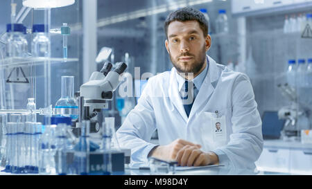 Young Male Research Scientist Talks Into Camera. He's Sitting in a High-End Modern Laboratory with Beakers, Glassware, Microscope and Working Monitors - Stock Photo