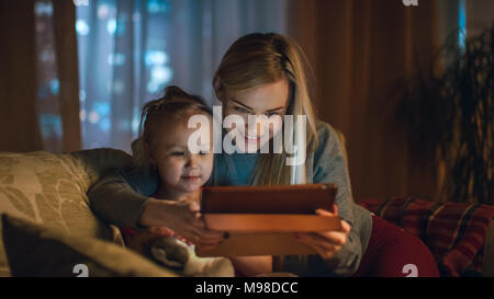 Beautiful Mother and Her Little Daughter are Sitting on a Sofa in the Living Room, They Use Tablet Computer. It's Evening, Room is Cozy and Warm. - Stock Photo