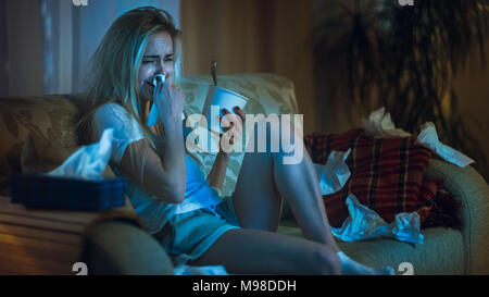 In the Evening Heartbroken Girl Sitting on a Sofa, Crying, Using Tissues, Eating Ice Cream and Watching Drama on TV. Her Room is in Mess. - Stock Photo