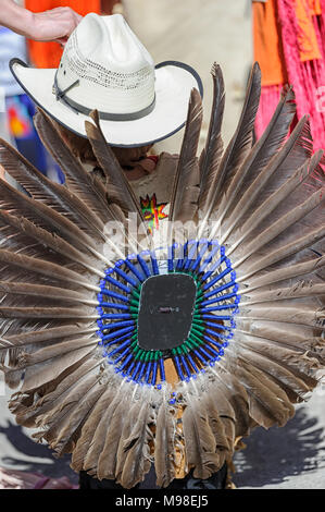 Native male wearing a cowboy hat and an eagle feather  bustle (regalia) at the Calgary Stampede in Canada - Stock Photo
