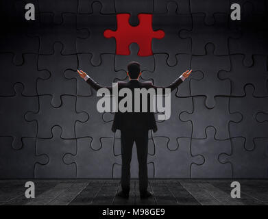 Problem in Work Concept. Businessman Standing in front of blank Jigsaw Puzzle Wall to Finding a Lost Piece. Teamwork or Human Resource - Stock Photo