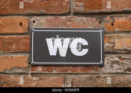 Toilet WC sign on old red brick wall. White WC sign on black metal plate. Outdoor sign. - Stock Photo