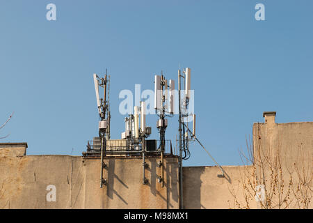 Mobile antenna on the roof of a building against blue sky. Broadcasting and network communicators, receivers. Modern phone and communication tech - Stock Photo