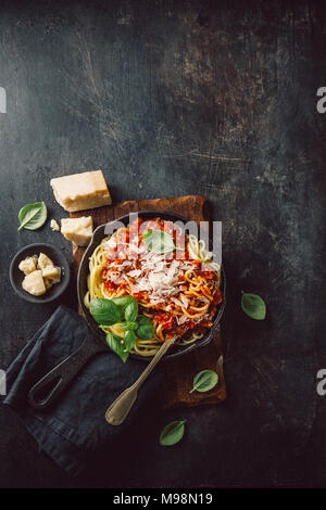 From above appetizing pasta with cheese and tomato sauce on dark background. - Stock Photo