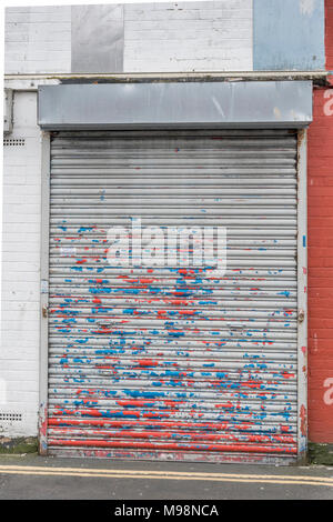 Battered closed roller shutter door with paint peeling off. Metaphor recession, high street closures, vacant shops. Obstructed or obstruction concept. - Stock Photo