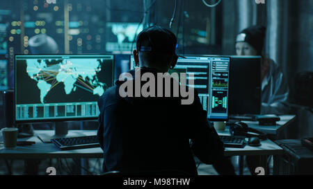 Back View of Teenage Hacker Working in Computer and Infecting with Virus Data Servers of Government Infrastructures. His Hideout is Dark with Monitors - Stock Photo