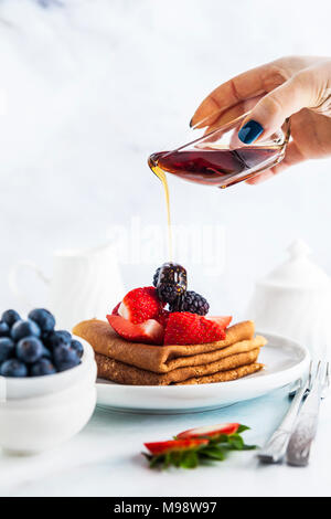 pour maple syrup on Traditional Ukrainian or Russian pancakes with fresh berries and sauce on the table - Stock Photo