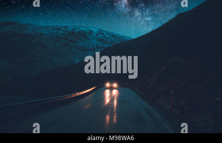 Norway adventures, night road trip under the stars, traveling in the car at nighttime, driving along hight snowy mountains, freedom concept - Stock Photo