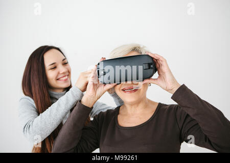 A young girl explains to an elderly woman how to use virtual reality glasses. The older generation and new technologies. - Stock Photo