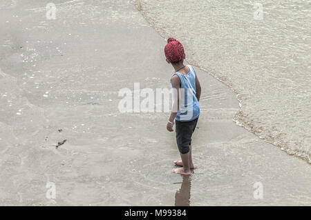 a boy stands in the shallow water of the sea with a red cloth on his head - Stock Photo