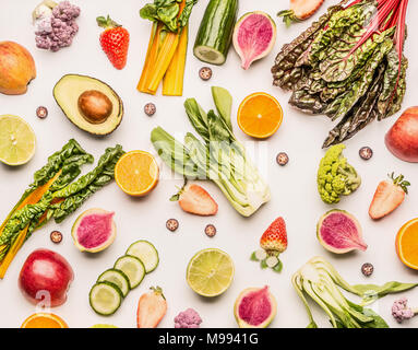 Colorful fruits and vegetables flat lay background with half of oranges,avocado, citrus,apples and berries , top view. Healthy food and clean eating i - Stock Photo