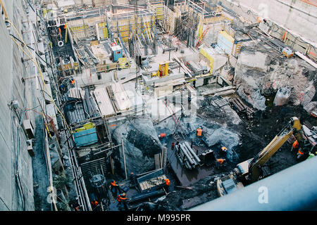 A foundation base of a future building with workers in orange vests and machinery. View from above at some angle. - Stock Photo
