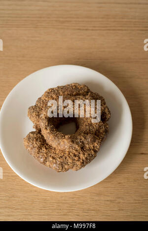 Cinnamon Donut on a White Plate on a Wood Table Overhead View - Stock Photo