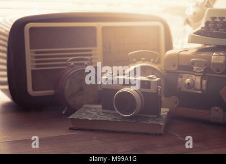 Vintage objects on a desk: suitcase, camera, radio and alarm clocks - Stock Photo