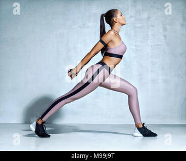 Warming up before training. Sporty woman in sportswear stretching legs on grey background. Strength and motivation. Side view - Stock Photo