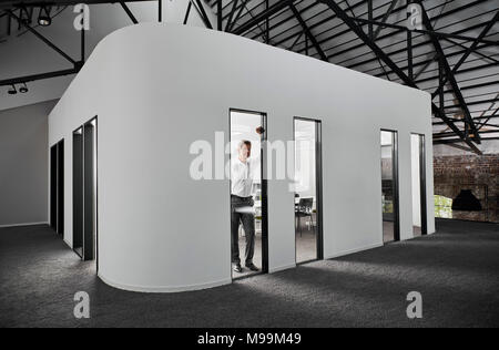 Businessman in modern conference room looking out of window - Stock Photo