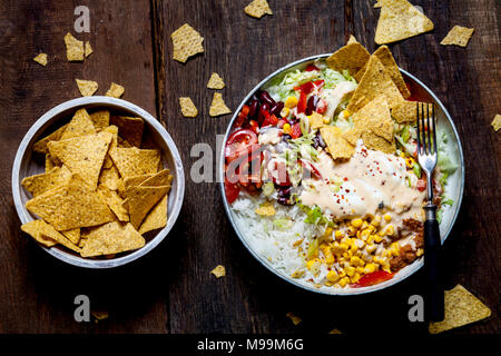 Taco salad bowl with rice, corn, chili con carne, kidney beans, iceberg lettuce, sour cream, nacho chips, tomatoes - Stock Photo