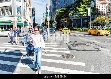 New York City, USA - October 28, 2017: Midtown Manhattan with people crossing street Columbus Circle, Broadway road in traffic by Starbucks - Stock Photo