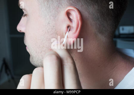 Close up shot of caucasian man cleaning his ears - Stock Photo