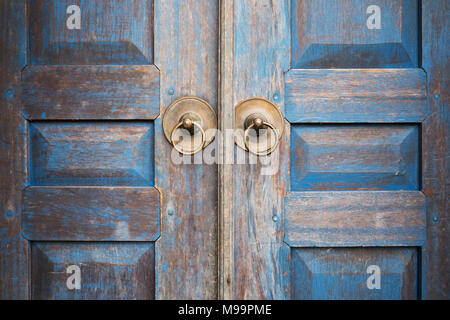Blue painted aged worn wooden door with metal circle handle - Stock Photo