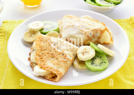 Crepes with banana and kiwi slices on white plate. Close up view - Stock Photo