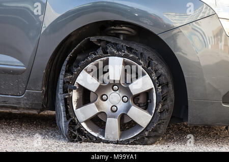 Destroyed blown out tire with exploded, shredded and damaged rubber on a modern suv automobile. Flat low profile tyre on an alloy rim, ripped open - Stock Photo