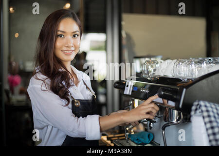 Asian women Barista smiling and using coffee machine in coffee shop counter - Working woman small business owner food and drink cafe concept - Stock Photo