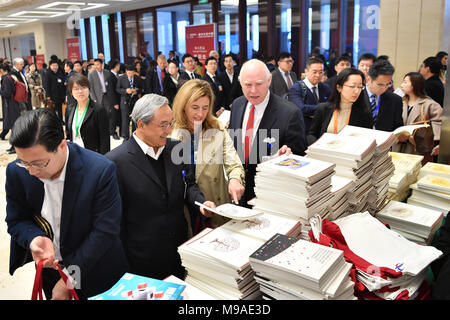 Beijing, China. 24th Mar, 2018. Attendees take handouts at the China Development Forum (CDF) Economic Summit in Beijing, capital of China, March 24, 2018. China Development Forum, hosted by the Development Research Center of the State Council, is being held from March 24 to 26. Credit: Li Xin/Xinhua/Alamy Live News - Stock Photo