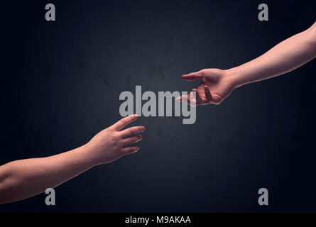 Two male hands reaching out to one another, almost touching, in front of dark clear empty background wall concept - Stock Photo