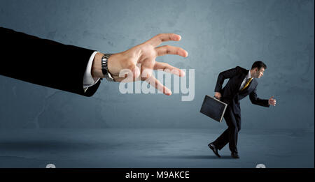 Business man running away from a huge hand concept on background - Stock Photo