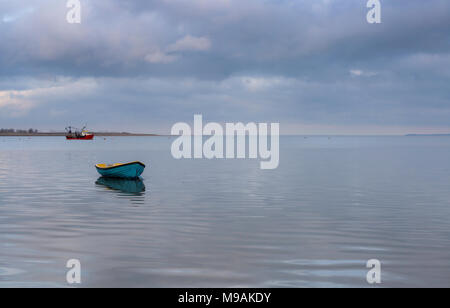Looking across the Swale estuary under a cloudy sky from Oare Marshes, Faversham, Kent towards the Isle of Sheppey. UK. Two small boats are visible. - Stock Photo
