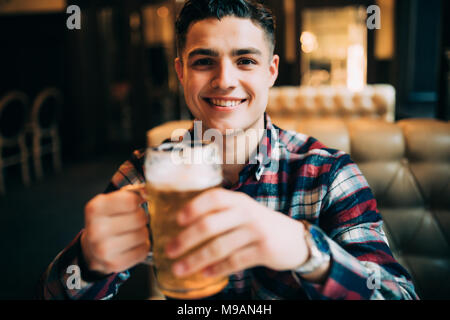 Man drinking beer. Young man drinking beer while sitting at the bar counter - Stock Photo
