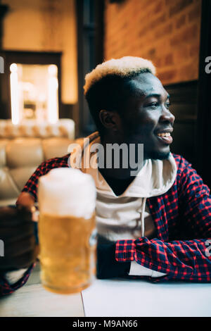 Happy handsome african american young man drinking beer - Stock Photo