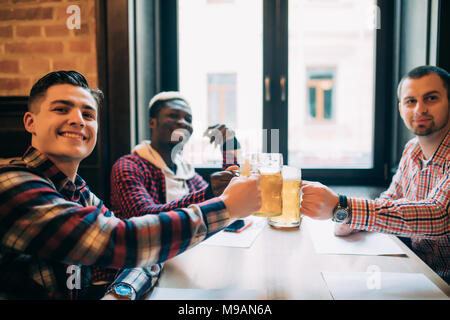 Group of happy young office workers clinking with beer at pub, looking at each other, smiling. - Stock Photo