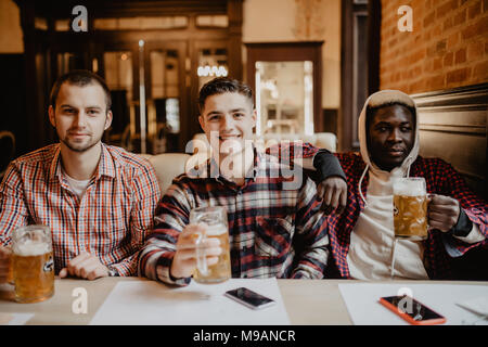 Meeting with the best friends. Three happy young men in casual wear talking and drinking beer while sitting in bar - Stock Photo