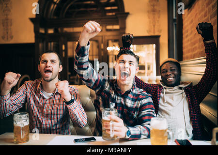 Happy football fans or male friends drinking beer and celebrating victory at bar or pub - Stock Photo
