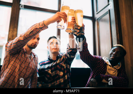 Multiracial friends men cheers with beer in glasses in pub. - Stock Photo