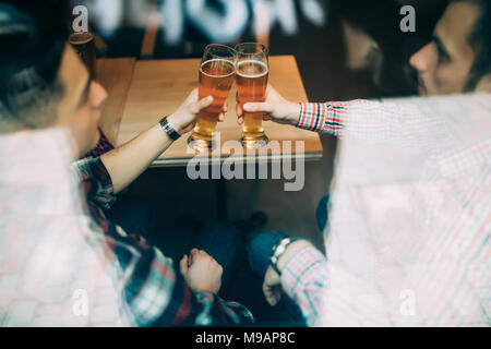 Multiracial old friends meet in pub and drink beer, talking and have fun view through window. - Stock Photo