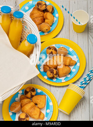 Summer picnic. Sweet picnic - orange juice and muffins, croissants and cakes on yellow and blue disposable dishes. Top view. - Stock Photo