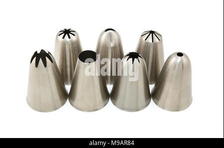 Seven metal icing nozzles for piping different shapes, arranged in two rows on a white background - Stock Photo