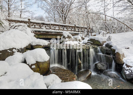 Snowclad Binnen Bridge above silky Binen falls after a Spring snowfall in Prospect Park, Brooklyn, New York. - Stock Photo