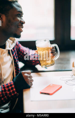 Handsome Afro American is drinking beer while resting in pub - Stock Photo