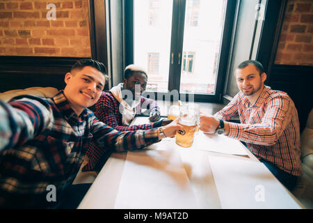 Cheerful old friends having fun by taking selfie and drinking draft beer in pub - Stock Photo
