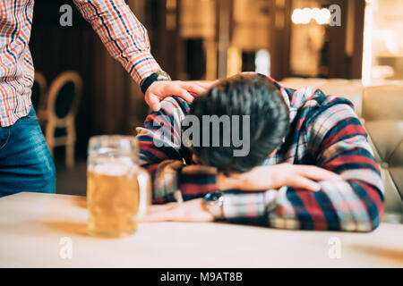 people, leisure, friendship and party concept - man with beer waking his drunk friend sleeping on table at bar or pub - Stock Photo