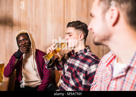 Three young men in casual clothes are smiling drinking beer while sitting at bar counter in pub - Stock Photo
